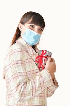 Cerca de una mujer joven con una mascarilla quirúrgica sosteniendo una caja de regalo cerca de su pecho sobre un fondo claro.