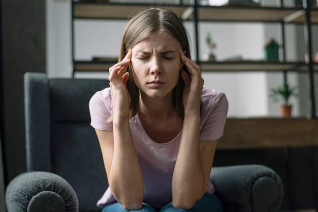 Cerca de una mujer joven que sufre de dolor de cabeza
