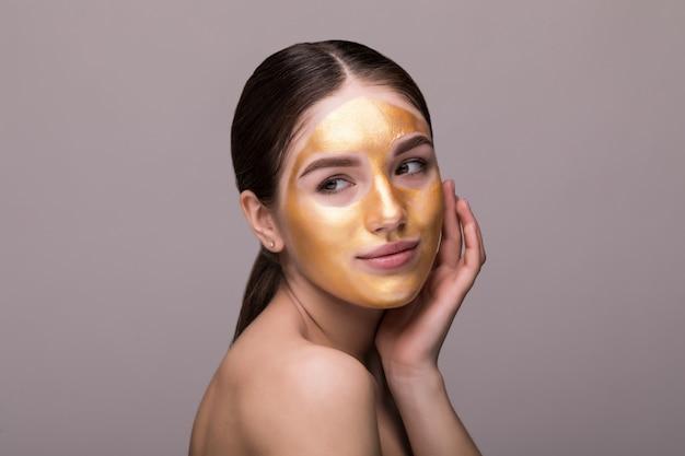 Cerca de mujer joven sana con oro cosmética mascarilla sobre piel suave.