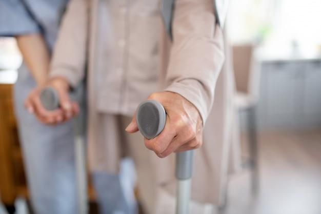 Cerca de la mujer jubilada con muletas mientras camina