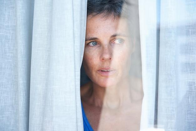 Cerca de una mujer mayor que mira abriendo cortinas y mirando por la ventana