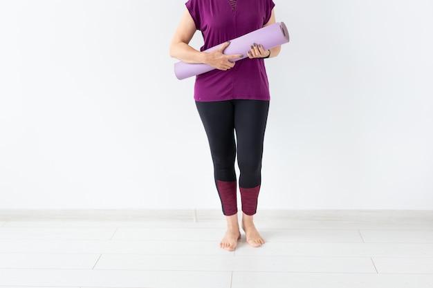 Cerca de una mujer de mediana edad después del yoga con su estera sobre fondo blanco.