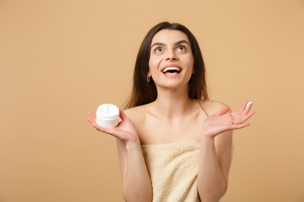 Cerca de mujer medio desnuda con piel perfecta maquillaje desnudo aplicando crema facial aislada en la pared de color beige pastel