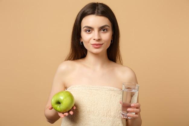 Cerca de mujer medio desnuda con piel perfecta, maquillaje desnudo sostiene manzana y agua aislada en la pared de color beige pastel