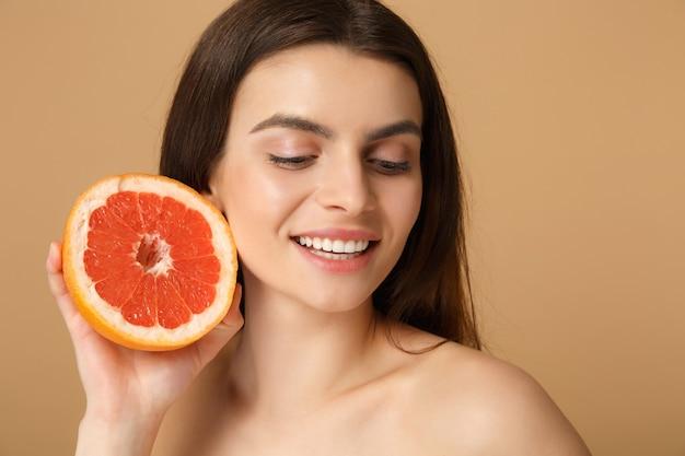 Cerca de la mujer medio desnuda con la piel perfecta maquillaje desnudo sostiene pomelo aislado en la pared de color beige pastel