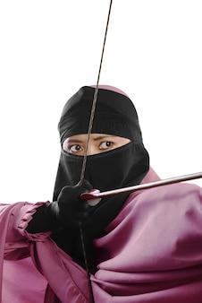 Cerca de la mujer musulmana asiática lista para disparar una flecha