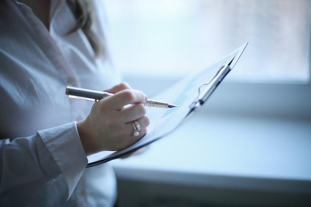 De cerca. mujer de negocios comprobando el cronograma financiero .foto con espacio de copia