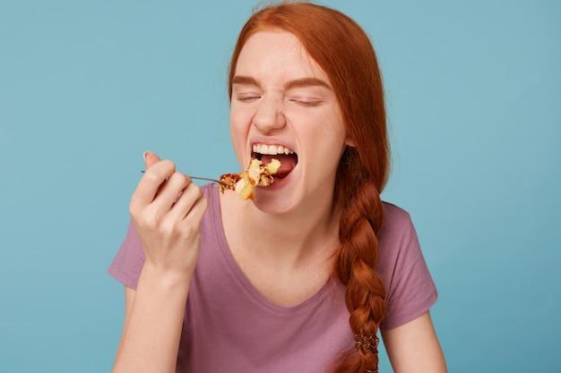 Cerca de la mujer pelirroja con los ojos cerrados, estira la cuchara a la boca come un pastel alto en calorías