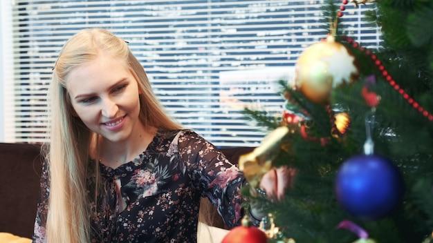 Cerca de mujer sonriente colgando bolas en el árbol de navidad