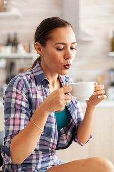 Cerca de mujer sosteniendo una taza de té verde caliente tratando de beberlo