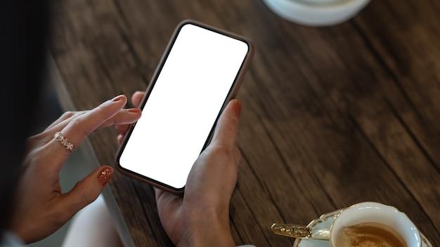 Cerca de mujer sosteniendo teléfono móvil con pantalla en blanco en blanco