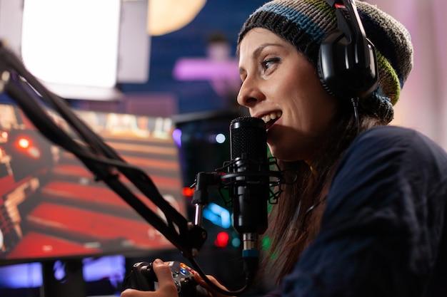 Cerca de la mujer streamer hablando por un micrófono profesional en el estudio de la casa. transmisión en línea de torneos de juegos cibernéticos utilizando tecnología de red inalámbrica