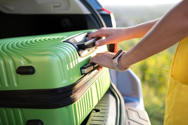 Cerca de la mujer tomando la maleta verde del maletero del coche.