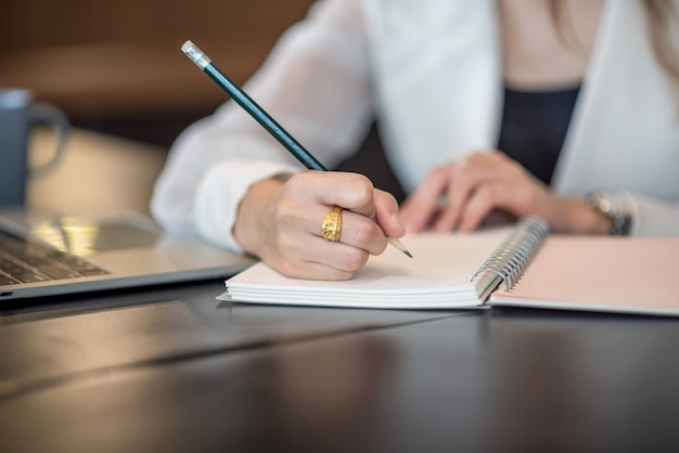 Cerca de mujer tomando notas sobre el escritorio en la oficina