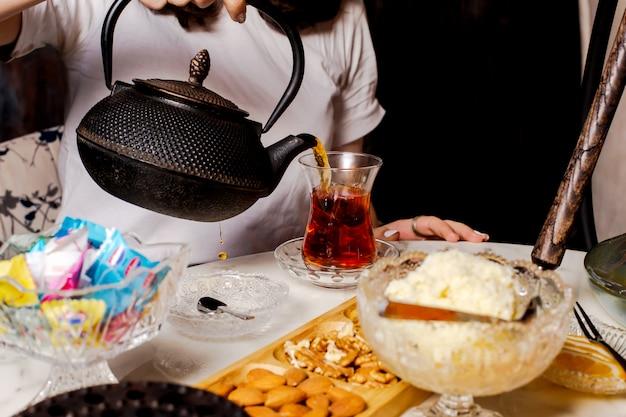 Cerca de mujer vertiendo té negro de tetera de hierro fundido negro