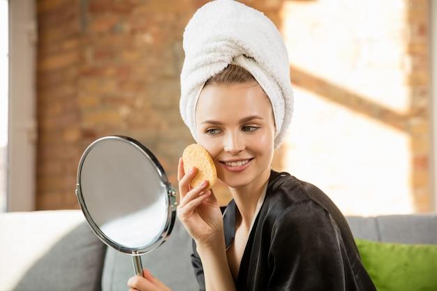 Cerca de mujer vestida con bata de seda haciendo su rutina diaria de cuidado de la piel en casa.