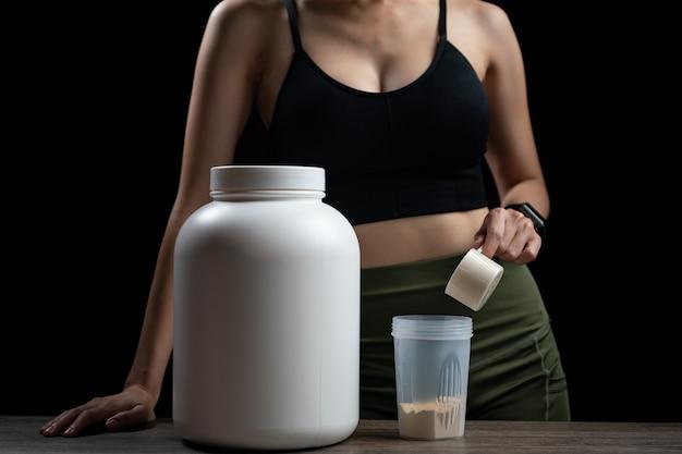 Cerca de mujeres con cucharada de medición de proteína de suero, jarra y botella agitadora, preparando batido de proteínas.
