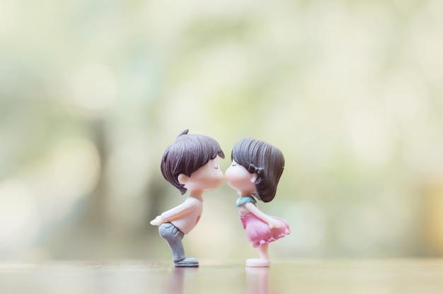 Cerca de muñecas mini pareja en beso romántico