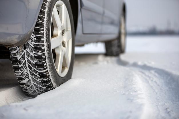 Cerca de un neumático de automóvil estacionado en camino nevado en día de invierno