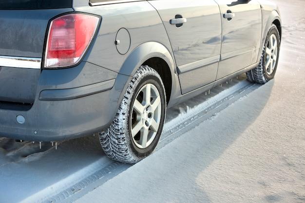 Cerca de un neumático de automóvil estacionado en una carretera nevada el día de invierno.