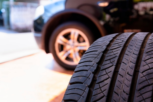 Cerca del neumático viejo con rueda de coche. taller de neumáticos y cambio de rueda vieja del coche.