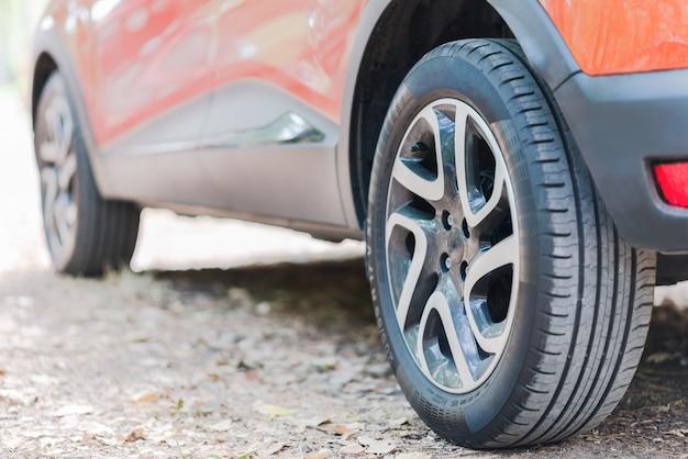 Cerca de neumáticos de coche. vista posterior de un automóvil estacionado sobre una carretera cubierta de hojas de otoño.