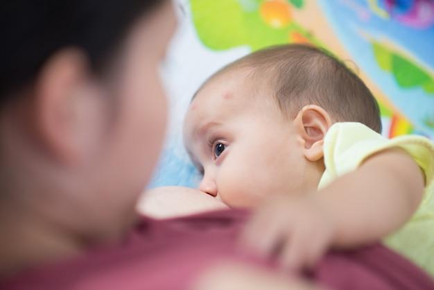 Cerca de la niña chupando su mothere amamantamiento establecen lado