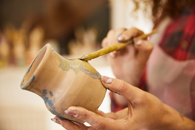 De cerca, la niña pinta un jarrón antes de hornear