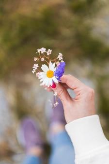 De cerca. la niña sostiene flores silvestres en una mano.