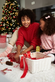 Cerca de niñas empacando regalos para navidad