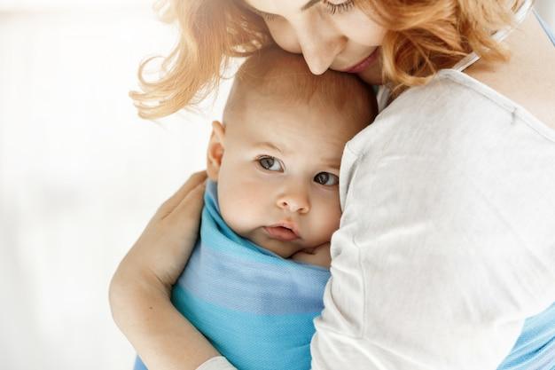 Cerca de un niño pequeño con grandes ojos grises mirando a un lado en brazos de madre encantadora