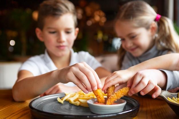 Cerca de niños sonrientes comiendo comida rápida