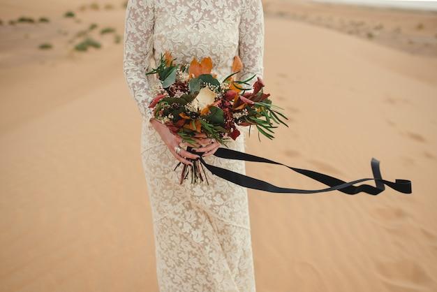 Cerca de una novia caucásica manos sosteniendo un hermoso ramo de flores