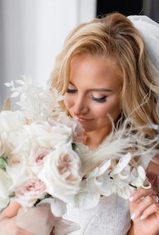 Cerca de la novia rubia con maquillaje natural, vestida con ropa de boda, sosteniendo un ramo de flores y disfrutando de su olor