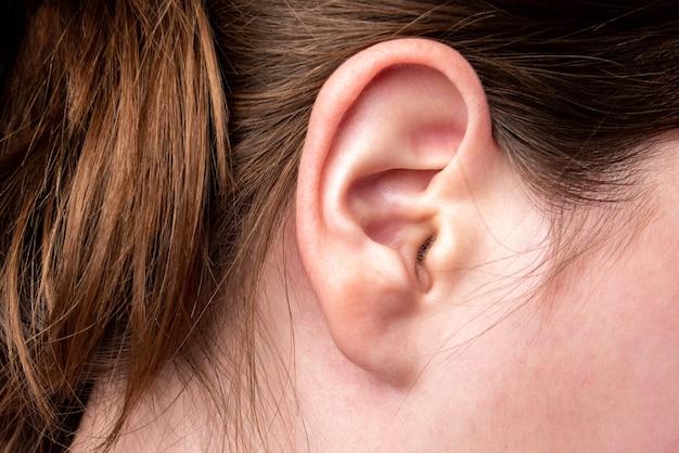 Cerca del oído femenino con fuente de dolor. dolor de oidos.