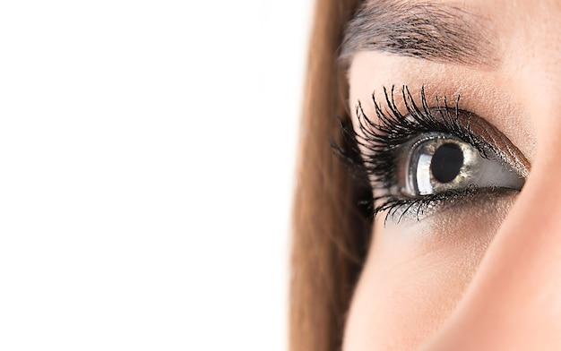Cerca del ojo abierto de una mujer mirando hacia arriba