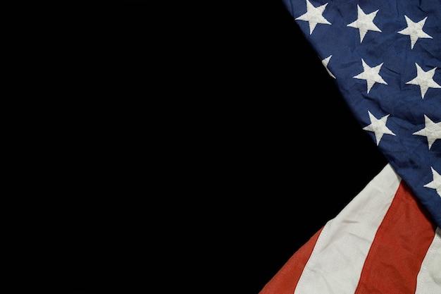 Cerca de ondeando la bandera americana nacional de estados unidos sobre fondo negro.