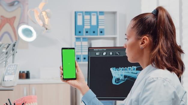 Cerca de ortodoncista sosteniendo smartphone con pantalla verde