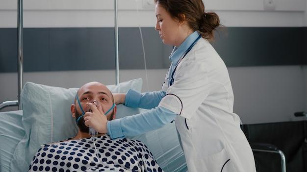 Cerca del paciente enfermo descansando en la cama mientras el médico pone máscara de oxígeno