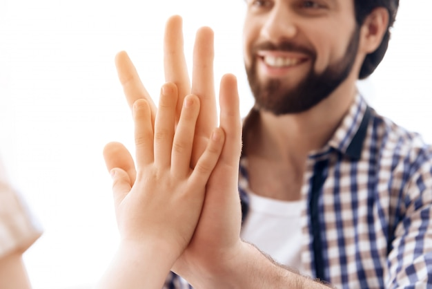 De cerca. padre alegre e hijo se dan cinco el uno al otro.