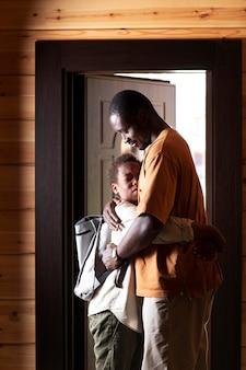 De cerca a los padres preparando a su hijo para la escuela