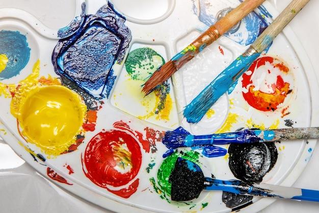 De cerca. paleta de arte con tubos de pinturas de acuarela y pinceles.
