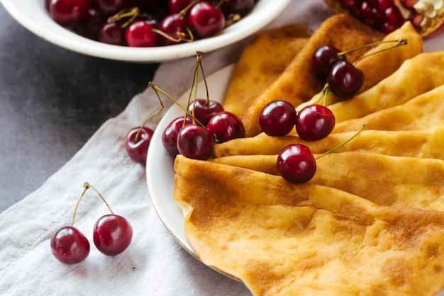 Cerca de panqueques y desayuno de cerezas.