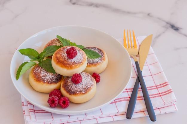 Cerca de panqueques de queso, syrniki, buñuelos de cuajada con frambuesas frescas en un tble. desayuno sabroso y alimentación saludable.