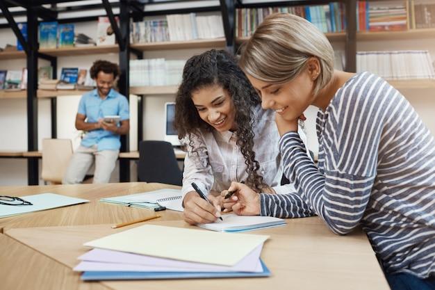 Cerca de un par de hermosas jóvenes estudiantes multiétnicas niñas haciendo la tarea juntas, escribiendo ensayos para la presentación, preparándose para los exámenes con buen humor