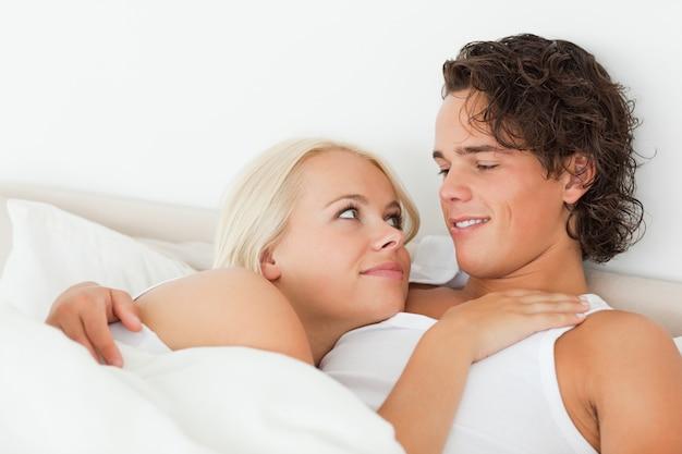 Cerca de una pareja acostada en una cama abrazando