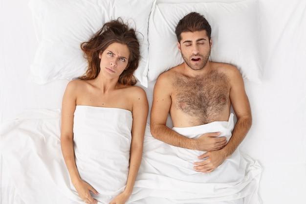 Cerca de la pareja acostada en la cama bajo una manta blanca