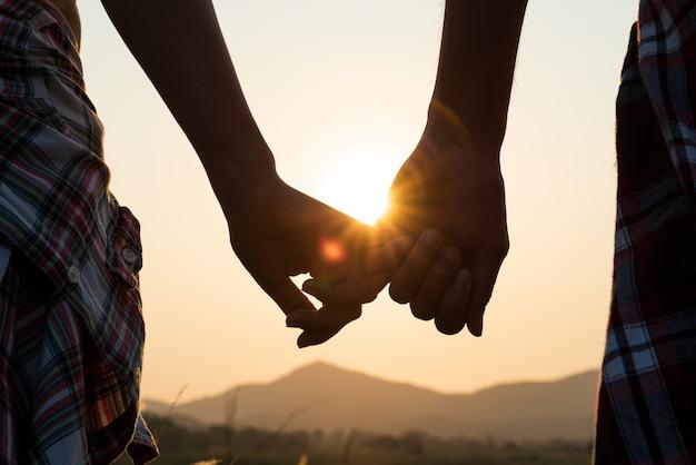 Cerca de pareja amorosa cogidos de la mano mientras caminaba al amanecer