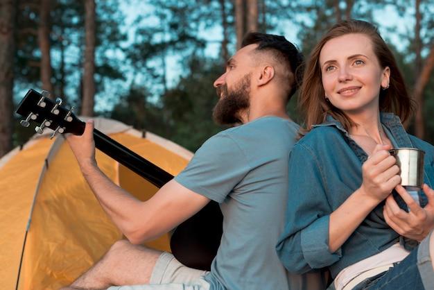 Cerca de la pareja de camping espalda con espalda