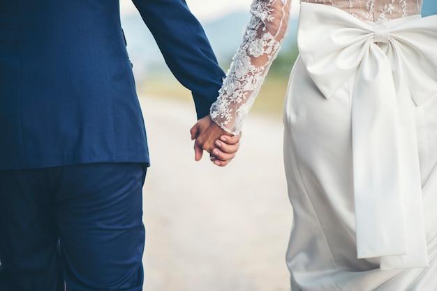Cerca de la pareja casada tomados de la mano en el día de la boda